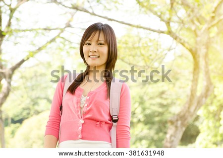 Young Asian college girl student standing on campus lawn, with backpack and smiling. - stock photo