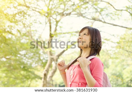 Young Asian college girl student standing on campus lawn, with backpack looking away and smiling. - stock photo