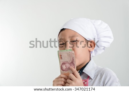 Young Asian cook holding Thai Baht in his hand and kissing. - stock photo
