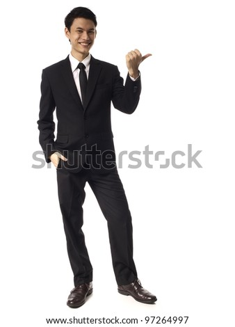 Young Asian Corporate Man pointing with thumb over white background