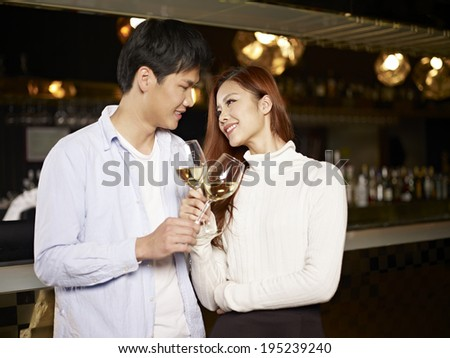 young asian couple enjoying a conversation in bar. - stock photo