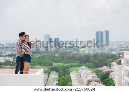 Young Asian couple enjoying the view from the roof - stock photo