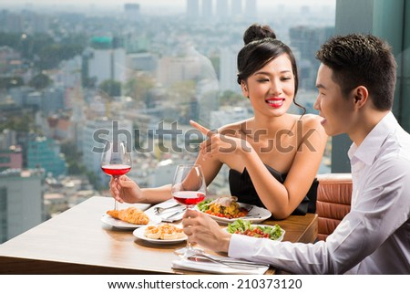 Young Asian couple having dinner in a luxurious restaurant - stock photo