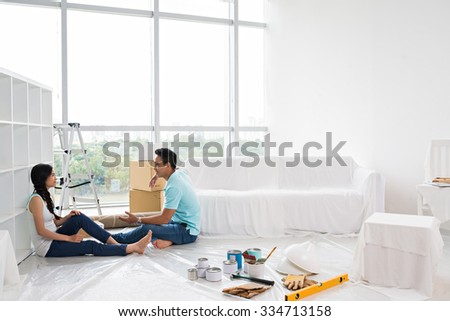 Young Asian couple making repairs in the apartment - stock photo