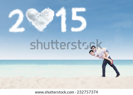 Young asian couple piggyback on beach with heart shaped cloud number 2015 - stock photo
