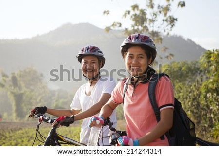 Young asian couple riding bicycle outside. Healthy Lifestyle  - stock photo