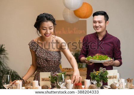Young Asian couple serving table for party at home