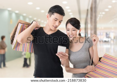 Young Asian couple shopping and looking at cellphone, closeup portrait. - stock photo