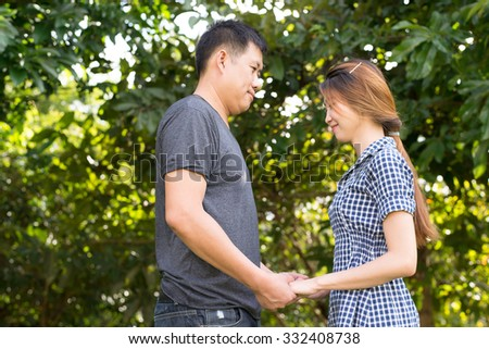 young Asian couple smile and hug each other with romantic mood and tone effect for conceptual use as wedding, romantic, loves, emotion, use purpose (with selective focus technique) - stock photo