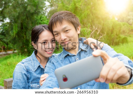 Young asian couple take selfie in park - stock photo