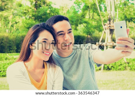 Young Asian couple taking selfie in the park, vintage tone