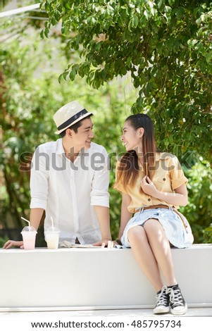 Young Asian couple talking during date in the park