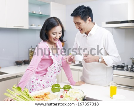 young asian couple talking in kitchen. - stock photo