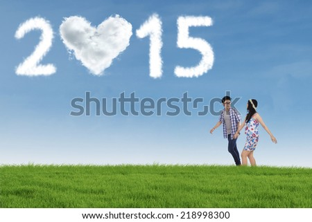 Young asian couple walking on meadow while  holding hands with heart shaped cloud number 2015