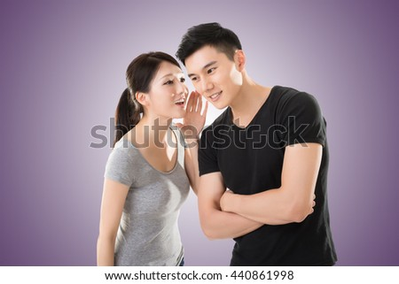 young Asian couple whisper, closeup portrait. - stock photo