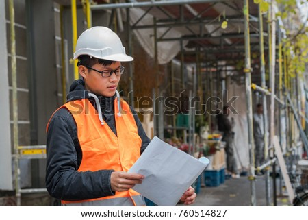 Young Asian engineer at work on construction site
