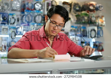 Young asian entrepreneur owning a computer shop and checking bills and invoice with calculator, doing budget and reviewing taxes.  - stock photo