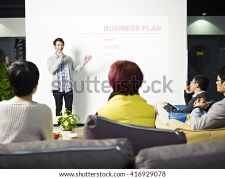 young asian entrepreneur presenting business plan for new project to angel investors. - stock photo