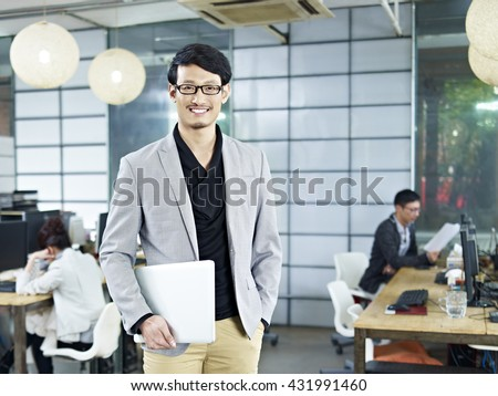 young asian entrepreneur standing in office with laptop computer under arm. - stock photo