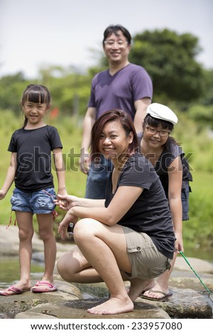 Young Asian family bonding time in park - stock photo