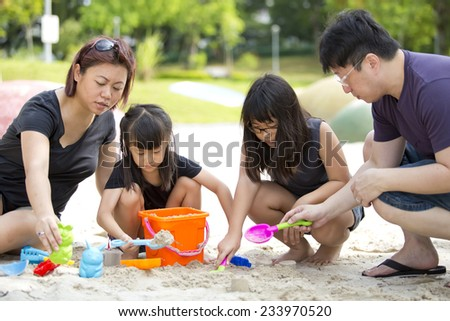 Young Asian family playing sand and bonding in park - stock photo