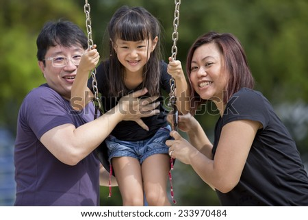 Young Asian family playing swing and bonding in park