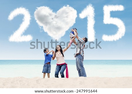 Young asian family spending time together at beach under cloud of 2015 - stock photo