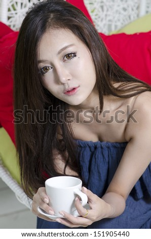 Young Asian female enjoying desserts - stock photo