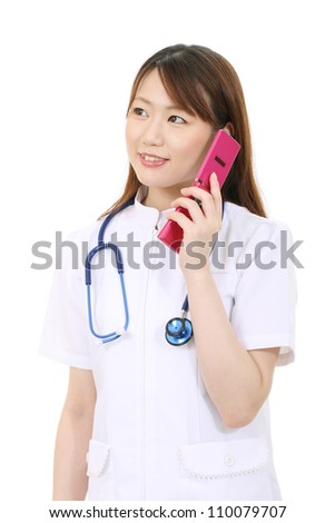 Young asian female nurse calling by cellular phone