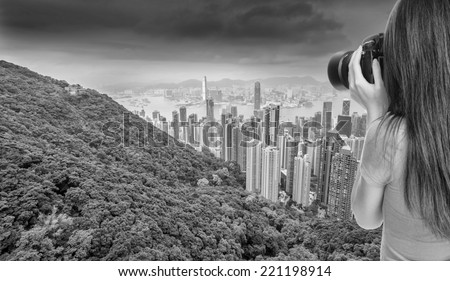 Young asian female photographer taking a picture of Hong Kong skyline. - stock photo
