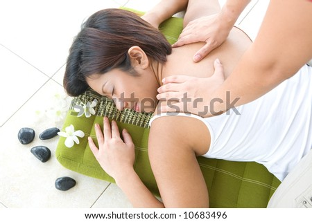 Young Asian female receiving back massage in spa as part of beauty and healthcare modern lifestyle. - stock photo