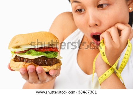 Young Asian female surprisingly looking at burger and holding measuring tape o the other hand