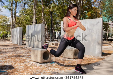 Young Asian fitness woman doing exercises in the park - stock photo