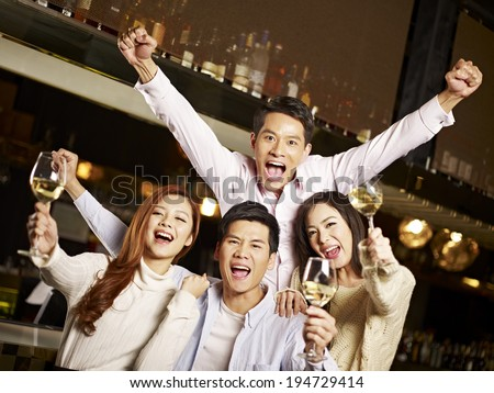 young asian friends couples enjoying party in pub - stock photo