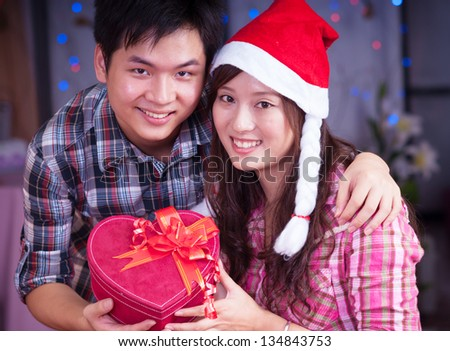 young asian girl and boyfriend with a present box at christmas