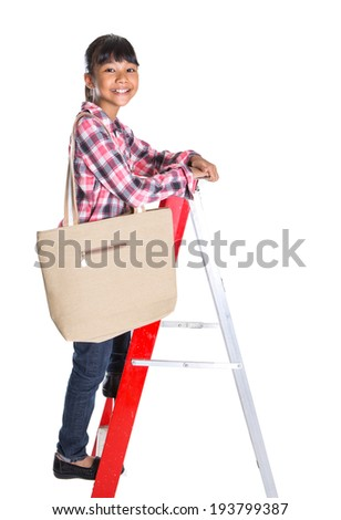 Young Asian girl climbing a ladder with a sling bag over white background