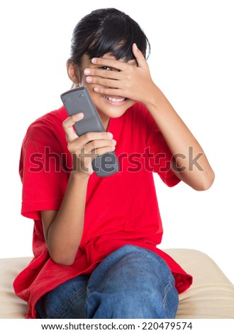 Young Asian girl covering her face with her hand while holding television remote control device over white background - stock photo