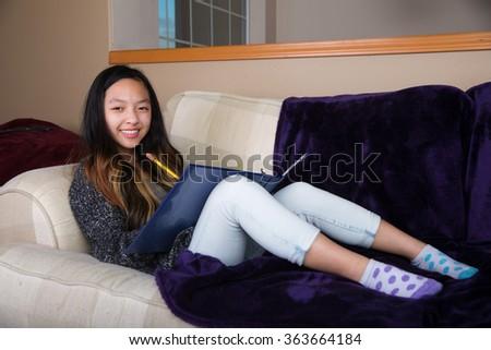 Young Asian girl doing homework - stock photo