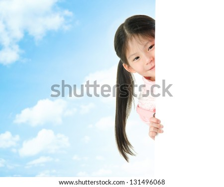 Young Asian girl hiding behind a blank white card in summer day, blue sky as background. - stock photo