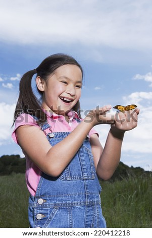 Young Asian girl holding butterfly outdoors - stock photo