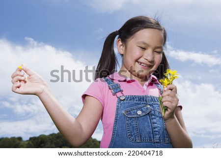 Young Asian girl holding flowers outdoors - stock photo