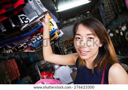 Young asian girl in local shop buying clothes