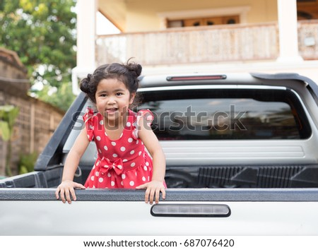 Young Asian Girl in Red Polka Dot Dress on Back of Pickup Truck