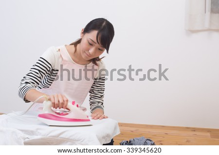 young asian girl ironing - stock photo