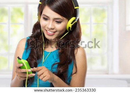 young asian girl listening music with headphones - stock photo