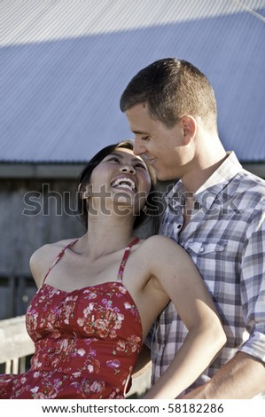 Young asian girl looking up a young man. - stock photo