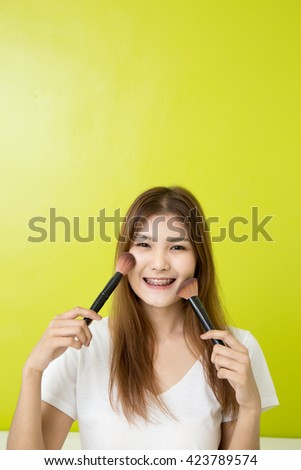 Young asian girl making up with cosmetics on green background