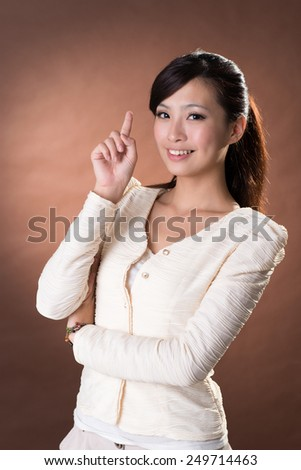 Young Asian girl portrait with smiling expression against brown studio background.