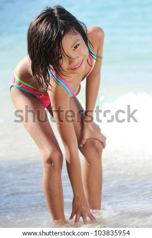 Young asian girl reaching for the sand in the beach. - stock photo