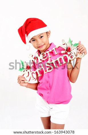 Young asian girl showing a christmas decoration. Isolated in light gray background. - stock photo
